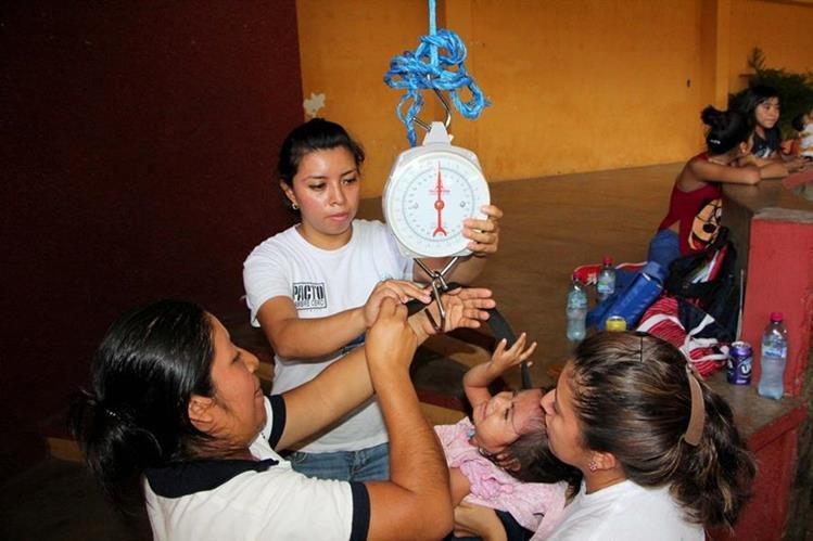 Personal de Salud pesa a una menor que padece desnutrición en Nuevo San Carlos, Retalhuleu. (Foto Prensa Libre: Rolando Miranda)