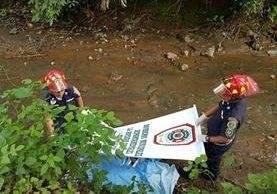 Socorristas resguardan el cuerpo que fue localizado en la orilla de un río. (Foto Prensa Libre: BMD)