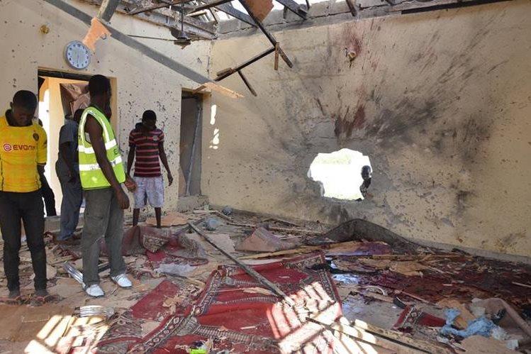 Personas observan el lugar donde ocurrió la explosión que dejó 28 muertos en Nigeria. (Foto Prensa Libre: AP).