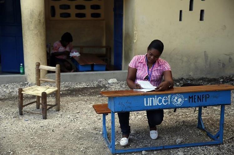 Una fiscal espera la apertura de un centro en el colegio República de Guatemala, en Haití. (Foto Prensa Libre: EFE)