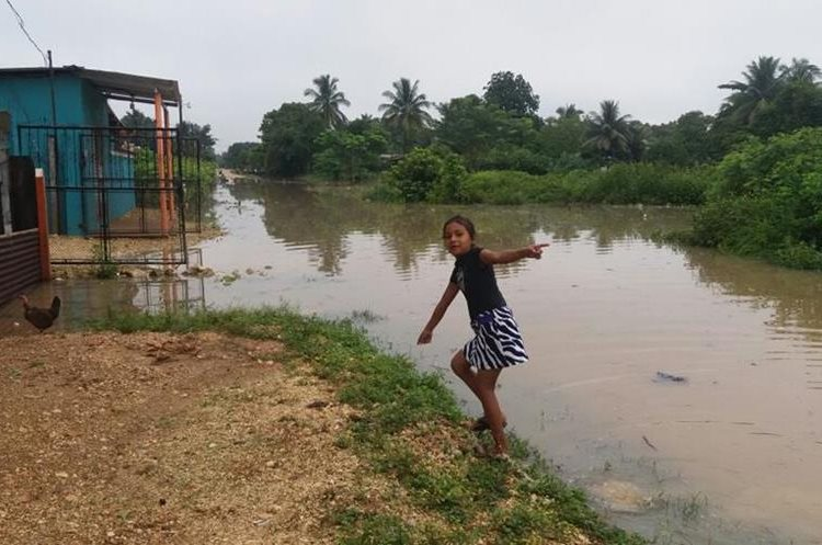 Una niña juega frente a lo que aparente ser un río, pero es una calle inundada. (Foto Prensa Libre: Rigoberto Escobar)