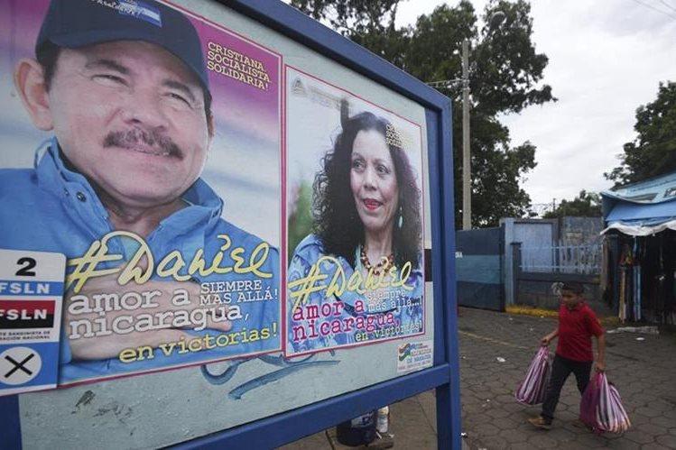 Un niño pasa frente a una valla del presidente Daniel Ortega y su esposa, Rosario Murillo. (Foto Prensa Libre: AFP).