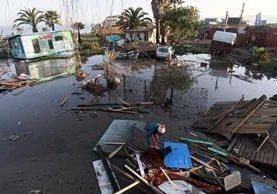 Una mujer camina entre los destrozos causado por el tsunami posterior al terremoto 8,4 en la escala de Richter que ayer por la noche sufrió Chile, en la localidad costera de Con Con, cerca de Valparaiso. (Foto Prensa Libre: EFE).