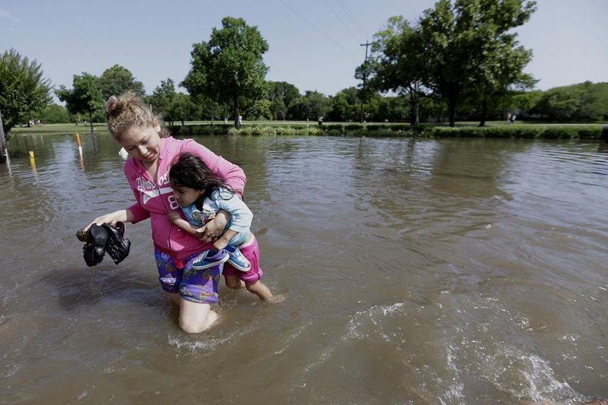 Nayeli Cervantes carga a la hija de una amiga, para librarla de la inundación que provocada por las lluvias. (Foto Prensa Libre: AP).