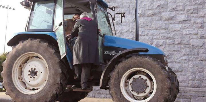 El sacerdote Paddy Mooney  sube a un tractor a imponer la ceniza al conductor. (Foto: @dailyedge)