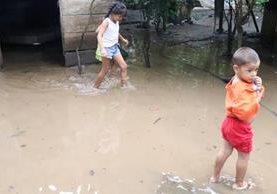 Niños caminan sobre el agua que se acumuló en el patio de su vivienda. (Foto Prensa Libre: Cristian I. Soto)