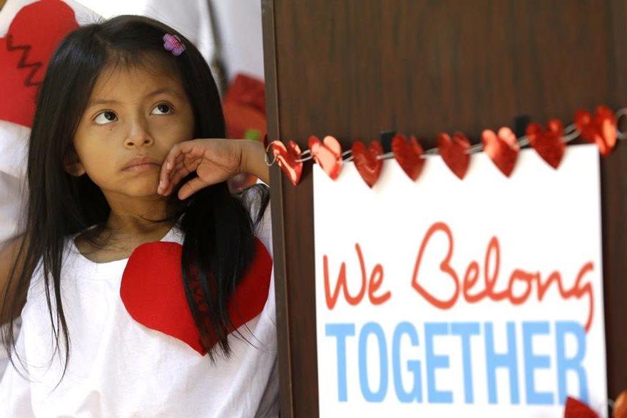 Una niña hija de padres indocumentados escucha las peticiones afuera del edificio del condado de Miami-Dade. (AP).