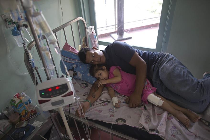 Ashley y su padre Maykol Pacheco en la camilla del hospital universitario de Caracas el pasado 11 de agosto. (Foto Prensa LIbre: AP).