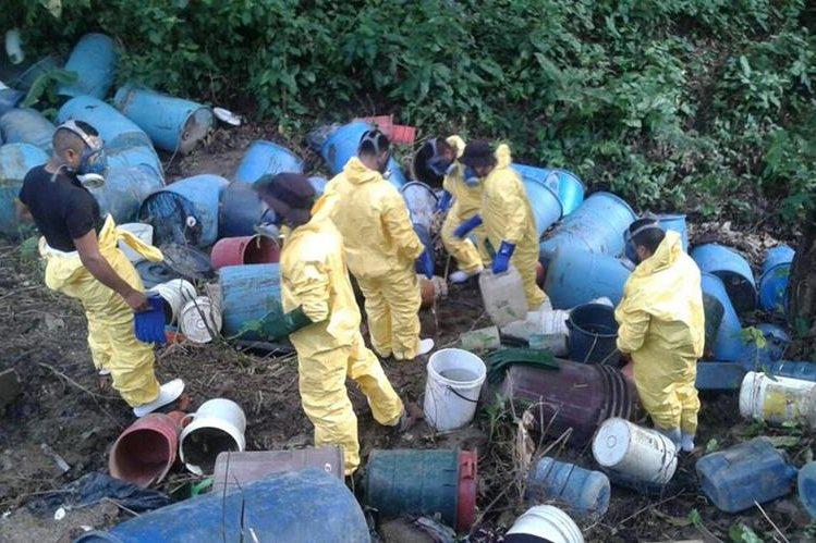 Agentes antinarcóticos efectúan exámenes en toneles localizados durante allanamiento en laboratorio de narcóticos, en Río Bravo. (Foto Prensa Libre: PNC)
