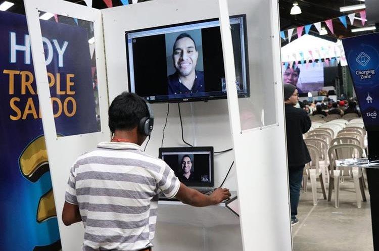 Un asistente de la cumbre habla con un familiar en EE. UU., en una cabina que habilitó Tigo para hacer videollamadas durante el foro. (Foto Prensa Libre: María José Longo)