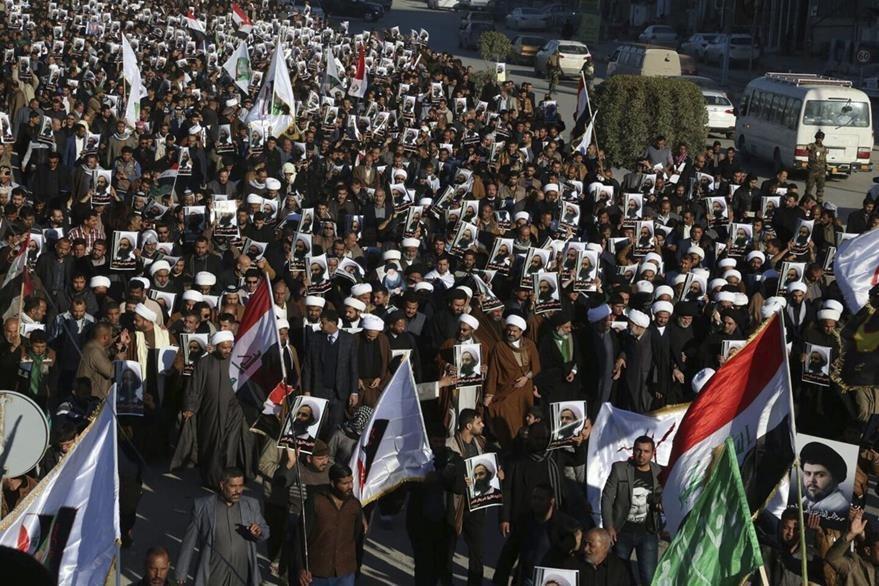 Cientos de personas portan retratos del clérigo opositor chií saudí, Nimr Baqir al Nimr durante una manifestación en Bagdad, Irak. (Foto Prensa Libre: EFE).