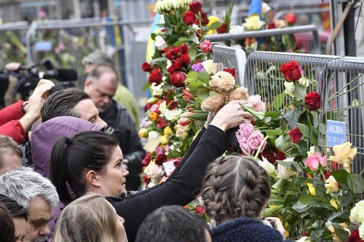Varias personas colocan flores en la escena del crimen en el centro de Estocolmo.(Foto Prensa Libre:EFE).