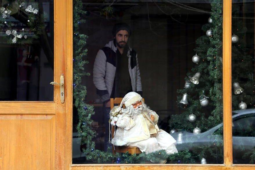 Un negocio sirio ofrece figuras de Santa Claus. (Foto Prensa Libre: AFP).