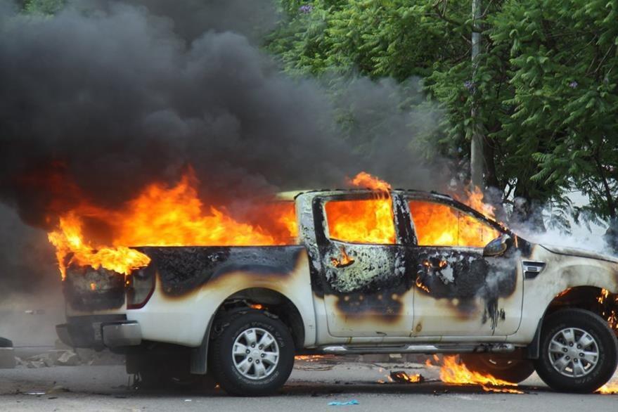 Un vehículo oficial es incendiado por maestros durante los enfrentamientos. (Foto Prensa Libre: EFE).