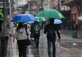 Guatemaltecos se cubren de la lluvia mientras caminan por la zona 1 capitalina. (Foto Prensa Libre: Hemeroteca PL)