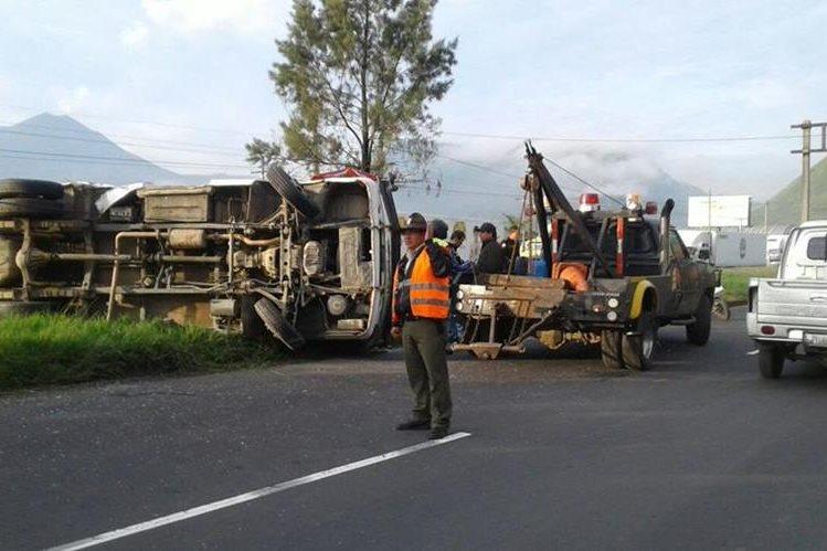 Una grúa intenta retirar del camino el microbús volcado en el kilómetro 30 de la ruta al Pacífico. (Foto Prensa Libre: Provial)