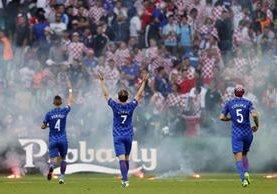 Los jugadores de la Selección de Croacia Ivan Perisic, Ivan Rakitic y Vedran Corluka trataron de calmar a sus seguidores. (Foto Prensa Libre: EFE)