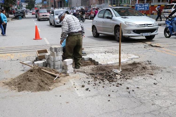 Un empleado de la Municipalidad de Quetzaltenango repara un bache con adoquín, lo cual, según expertos, no es adecuado. (Foto Prensa Libre: María José Longo)