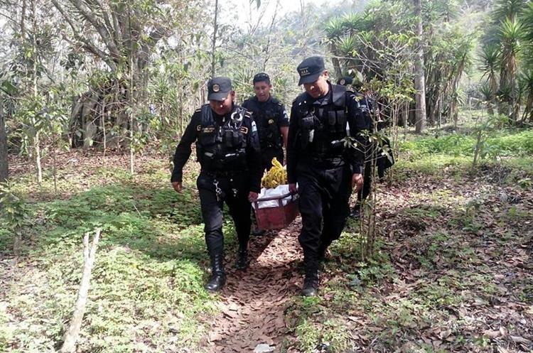 Agentes de la PNC trasladan el cadáver de una de las dos víctimas. (Foto Prensa Libre: Ángel Julajuj)