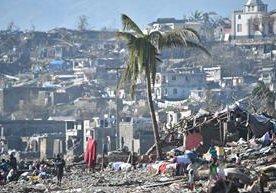 Personas caminan en medio de montones de escombros en Haití.