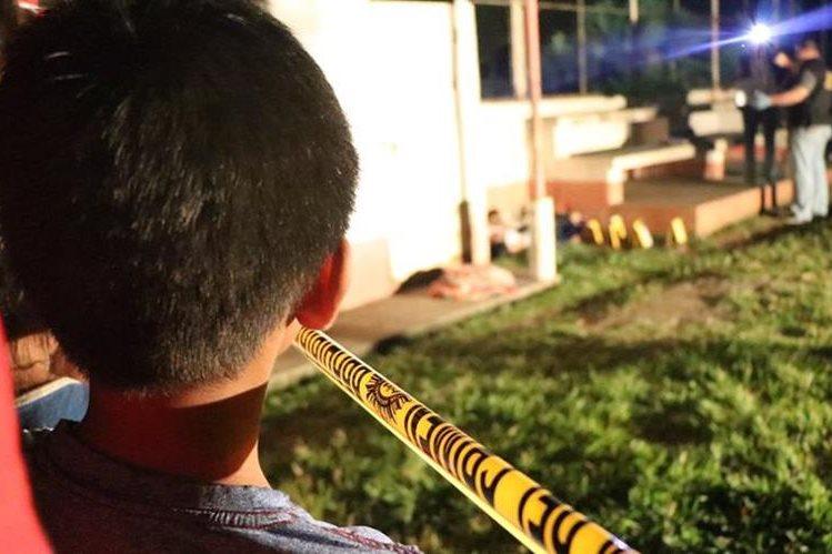 Vecinos de Cuyotenango, Suchitepéquez, observan los cuerpos de Mynor Efraín Vargas Chinchilla, de 23 años y Bernardino Xunac Pérez, 30, muertos a balazos. (Foto Prensa Libre: Cristian I. Soto)