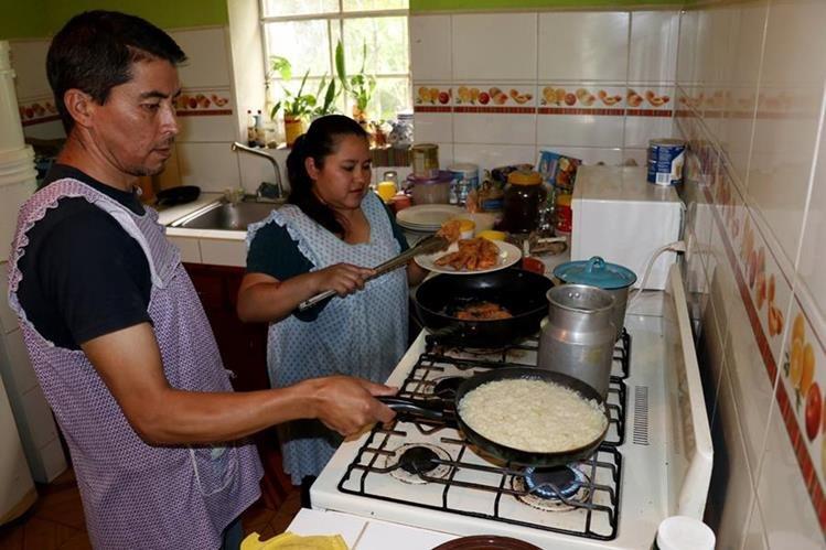 Lorenzo Castillo y Alma Gómez preparan carne de conejo para servir en el almuerzo. (Foto Prensa Libre: Mike Castillo)