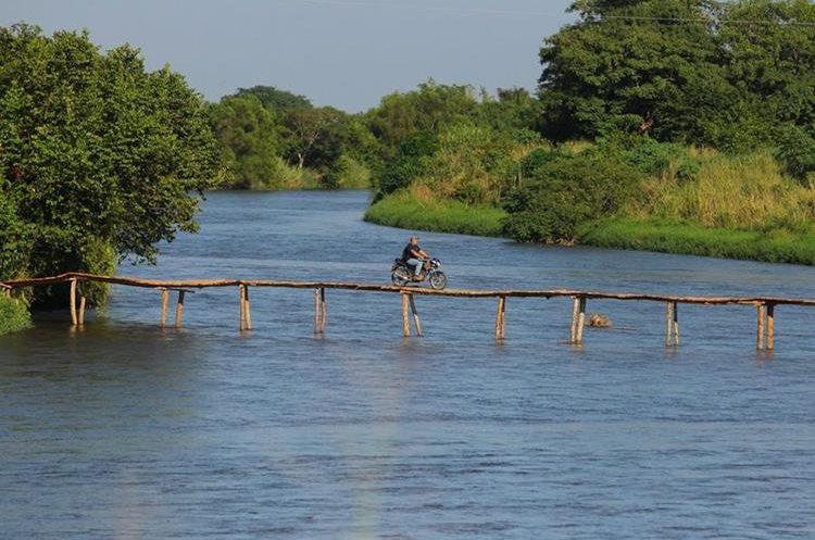 Motorista intrépido cruza un puente de madera, en Palo Blanco, Trocha Cuatro.