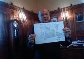 José Luis Chea Urruela, ministro de cultura y deportes, sostiene una imagen con la propuesta de una baranda que proteja el Palacio Nacional. (Foto Prensa Libre: Diario de Centro América)
