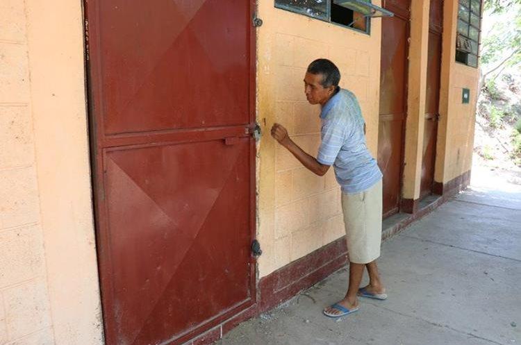 Un vecino muestra la puerta que dañaron los desconocidos para robar en la telesecundaria.  (Foto Prensa Libre: Mario Morales)