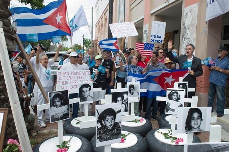 Vista de varias llantas con cruces blancas y fotografías de niños víctimas de la dictadura cubana durante una manifestación el domingo en el corazón de la Pequeña Habana, en Miami. (Foto Prensa Libre: EFE)