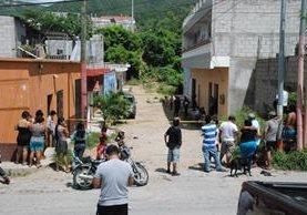 Vecinos de la colonia Linda Vista, zona 2 de Chiquimula, observan el lugar donde quedó el carro en el que murió baleada Belsy Rosmery Pérez Mejía. (Foto Prensa Libre: Mario Morales)