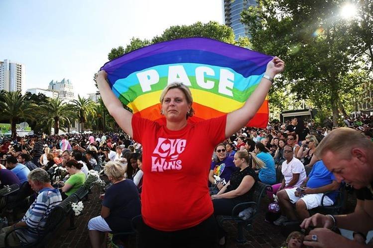 Una activista sostiene una bandera gay durante una muestra de solidaridad por la masacre en Orlando. (Foto Prensa Libre: AFP).