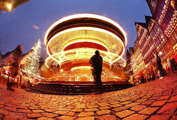 La gente observa un juego de luces en el mercado navideño en Frankfurt, Alemania. (AP).