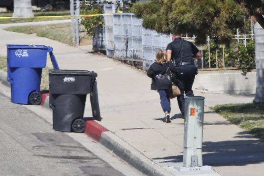 Un agente policial corre junto con el otro menor de edad que estaba en la casa con el presunto homicida atrincherado. (Foto Prensa Libre: AP).
