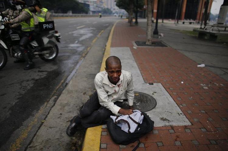 Un hombre cae al suelo al quedar herido durante la masiva protesta del jueves en Caracas.
