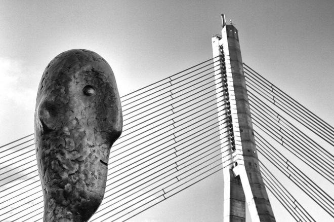 """""""La figura que da la espalda a la Torre de Riga, en Letonia, se mantiene igual durante cualquier estación, esté soleado o lloviendo, húmedo o seco. Me pregunto si se distrae con la belleza de los cables"""", dice el autor de su autor Oleg Dashkov: OLEG DASHKOV"""
