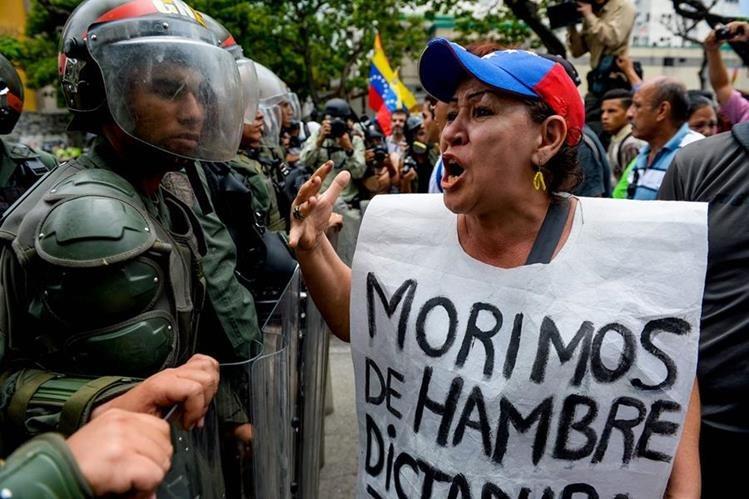Una mujer grita consignas contra las fuerzas de seguridad que reprimen marchas callejeras contra Maduro en Caracas, Venezuela. (Foto Prensa Libre: AFP).