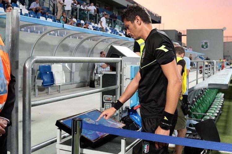 Antonio Damato observa el monitor en el partido de la Serie A entre el Genova y el Sassuolo. (Foto Prensa Libre: AP)