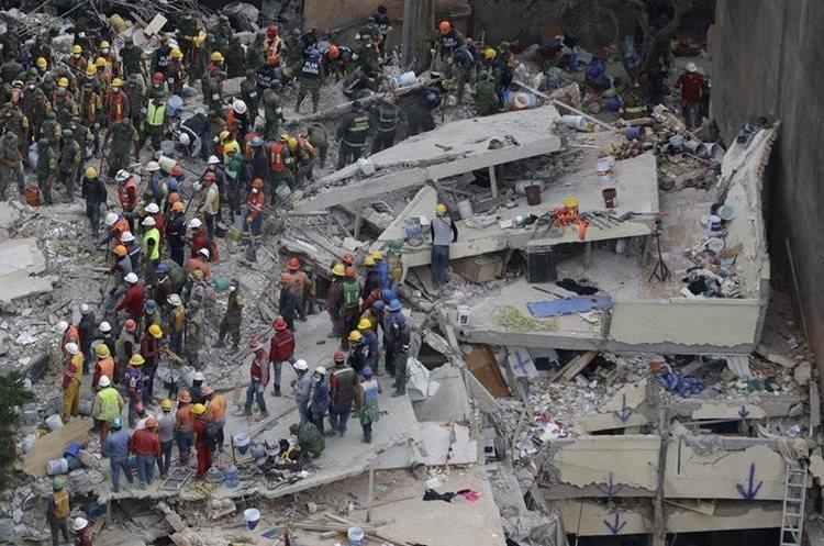 Recatistas buscan personas atrapadas dentro de un edificio colapsado en el área de Del Valle de la Ciudad de México. (AP).
