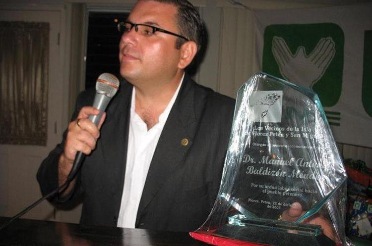 Baldizón muestra un reconocimiento que vecinos le entregan en 2007, cuando formaba parte del partido UNE. (Foto Prensa Libre: Hemeroteca PL)