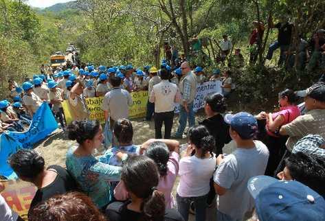 empleados de la mina, con cascos azules,  frente a los vecinos que bloquean el camino.