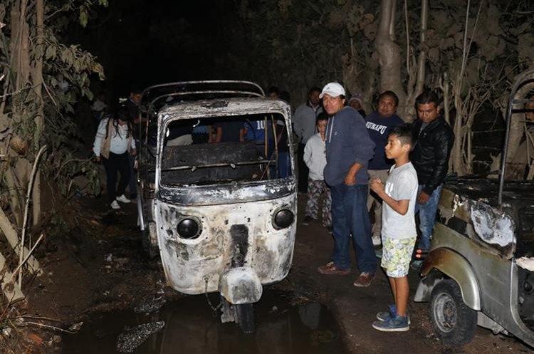 Curiosos observan los mototaxis incendiados en Jocotenango. (Foto Prensa Libre: Renato Melgar).