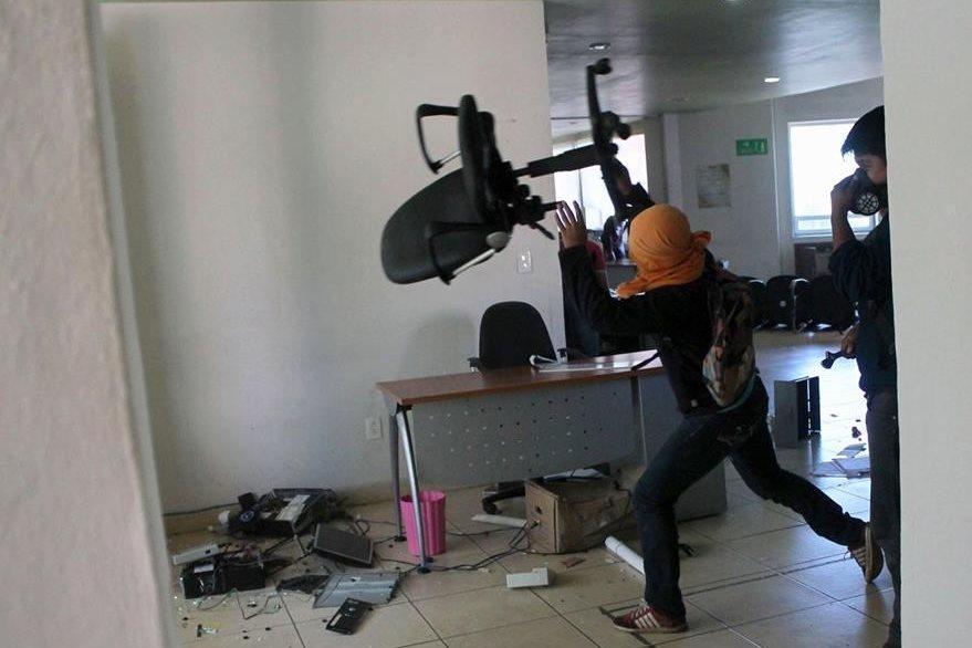 Un estudiante lanza una silla en el interior de la Fiscalía. (Foto Prensa Libre: AFP).