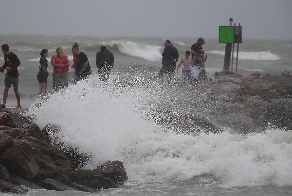 Varias personas disfrutan de las olas de la tormenta tropical Colin. (AFP).