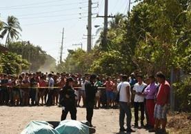 Curiosos permanecen en el lugar donde murió baleada la maestra, en Puerto San José, Escuintla. (Foto Prensa Libre: Enrique Paredes).