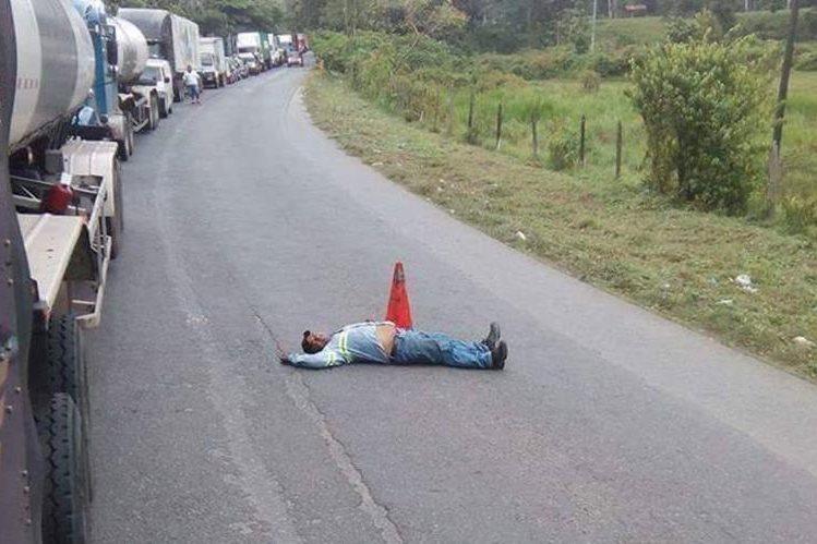 Santiago Morán permanece tirado en el asfalto para evitar que vehículos rebasen. (Foto Prensa Libre: Cortesía).