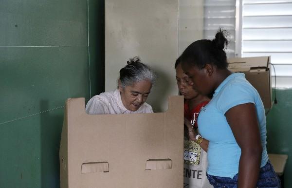 Una mujer acompañada de dos familiares vota en Santo Domingo.(EFE).