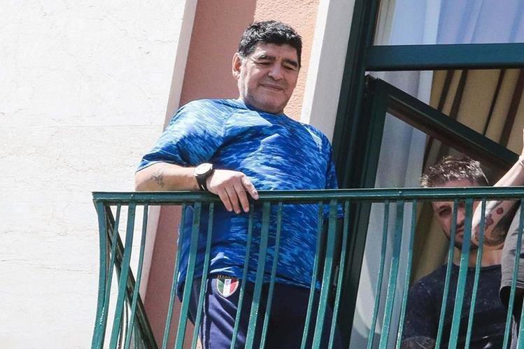 Diego Maradona saluda a sus seguidores desde la ventana del hotel en Nápoles. (Foto Prensa Libre: EFE)