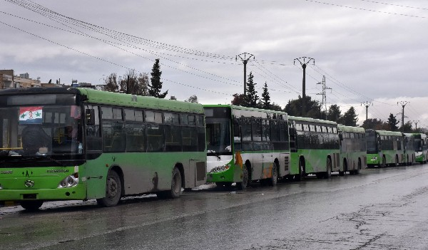 Autobuses esperan para evacuar a civiles que salen de las zonas controladas por los rebeldes de Alepo.(AFP).