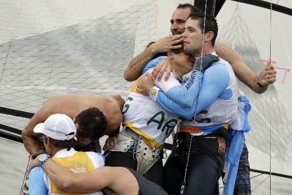 Atletas argentinos festejan la medalla de oro conseguida por Santiago Lange. (Foto Prensa Libre: AFP).